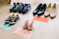 Zapatos del ` s de los niños al lado de un adulto Foto de archivo libre de regalías