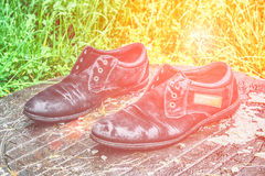 Zapatos del ` s de los viejos hombres Abandonado en la calle después de una lluvia Gastado y Foto de archivo libre de regalías