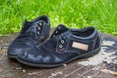 Zapatos del ` s de los viejos hombres Abandonado en la calle después de una lluvia Gastado y Fotos de archivo