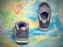 Zapatos del senderismo que caminan en el mapa del mundo Imagen de archivo libre de regalías