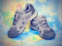 Zapatos del senderismo que caminan en el mapa del mundo Foto de archivo