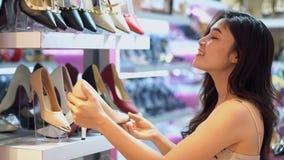 Zapatos del tacón alto de las compras de la mujer en una tienda almacen de video