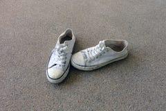 Zapatos del vintage, zapatillas de deporte blancas en fondo del piso Fotos de archivo