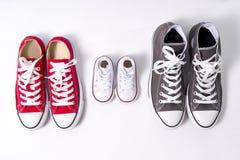 Zapatos en el padre grande, medio de la madre e hijo o pequeño tamaño del niño de la hija en concepto del amor de la familia Foto de archivo