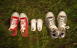 Zapatos en el padre grande, medio de la madre e hijo o pequeño tamaño del niño de la hija en concepto del amor de la familia Fotos de archivo