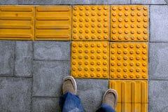 Zapatos en la pavimentación táctil del bloque para la desventaja ciega Foto de archivo libre de regalías