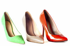Zapatos femeninos brillantes, multicolores en los tacones altos Fotos de archivo
