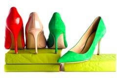 Zapatos femeninos brillantes, multicolores en los tacones altos aislados en el fondo blanco Fotografía de archivo libre de regalías
