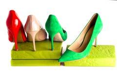 Zapatos femeninos brillantes, multicolores en los tacones altos aislados en el fondo blanco Imagenes de archivo