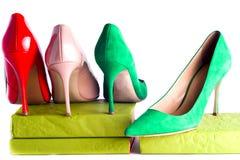Zapatos femeninos brillantes, multicolores en los tacones altos en el fondo blanco Foto de archivo libre de regalías