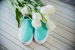 Zapatos femeninos con las flores en fondo de madera Fotos de archivo