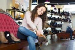 Zapatos femeninos de compra femeninos del invierno en zapatería Imagenes de archivo