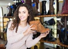 Zapatos femeninos de compra femeninos del invierno en zapatería Imagen de archivo libre de regalías