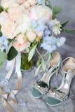 Zapatos femeninos del primer en los tacones altos cerca del ramo de flor imágenes de archivo libres de regalías