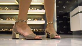 Zapatos femeninos que intentan en tienda almacen de metraje de vídeo