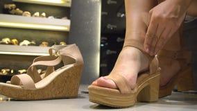 Zapatos femeninos que intentan en tienda metrajes