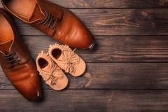 Zapatos grandes y pequeños en fondo de madera Imagen de archivo libre de regalías