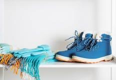 Zapatos, guantes y bufanda del invierno en el estante de madera blanco Fotos de archivo libres de regalías