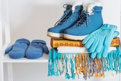 Zapatos, guantes y bufanda del invierno en el estante de madera blanco Imágenes de archivo libres de regalías