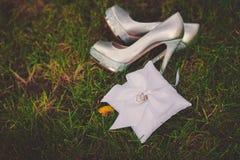 Zapatos hermosos de la boda con los tacones altos en la naturaleza, decoros Foto de archivo