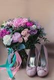 Zapatos hermosos de la boda con los tacones altos y un ramo de flores coloridas Foto de archivo libre de regalías