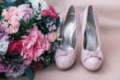Zapatos hermosos de la boda con los tacones altos y un ramo de flores coloridas Imagenes de archivo