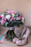 Zapatos hermosos de la boda con los tacones altos y un ramo de flores coloridas Fotos de archivo libres de regalías
