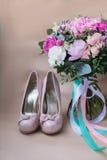Zapatos hermosos de la boda con los tacones altos y un ramo de flores coloridas Foto de archivo