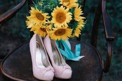 Zapatos hermosos de la boda con los tacones altos y un ramo de girasoles en una silla del vintage Imagen de archivo