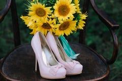Zapatos hermosos de la boda con los tacones altos y un ramo de girasoles en una silla del vintage Fotografía de archivo