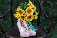 Zapatos hermosos de la boda con los tacones altos y un ramo de girasoles en una silla del vintage Fotos de archivo