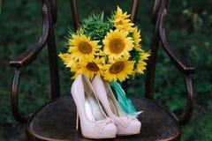 Zapatos hermosos de la boda con los tacones altos y un ramo de girasoles en una silla del vintage Imagen de archivo libre de regalías