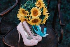 Zapatos hermosos de la boda con los tacones altos y un ramo de girasoles en una silla del vintage Fotografía de archivo libre de regalías