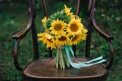 Zapatos hermosos de la boda con los tacones altos y un ramo de girasoles en una silla del vintage Imagenes de archivo