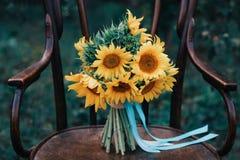 Zapatos hermosos de la boda con los tacones altos y un ramo de girasoles en una silla del vintage Imágenes de archivo libres de regalías