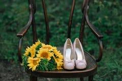 Zapatos hermosos de la boda con los tacones altos y un ramo de girasoles en una silla del vintage Fotos de archivo libres de regalías