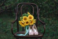 Zapatos hermosos de la boda con los tacones altos y un ramo de girasoles en una silla del vintage Foto de archivo libre de regalías