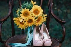 Zapatos hermosos de la boda con los tacones altos y un ramo de girasoles en una silla del vintage Foto de archivo