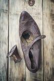 Zapatos llevados viejos en una tabla de madera Foto de archivo