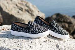 Zapatos modernos de las señoras en rocas Fotografía de archivo libre de regalías