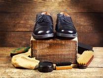 Zapatos negros con los accesorios del cuidado Fotografía de archivo