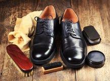 Zapatos negros con los accesorios del cuidado Imágenes de archivo libres de regalías