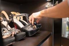 Zapatos negros de la moda del cuero de la señora en el estante de madera Imagen de archivo