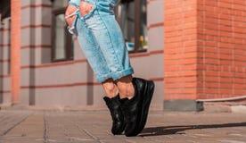 Zapatos negros de las zapatillas de deporte contra un fondo de la pared de ladrillo Foto de archivo libre de regalías