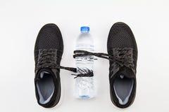 Zapatos negros del deporte con el cordón que sostiene la botella de agua de consumición en el fondo blanco foto de archivo libre de regalías