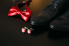 Zapatos negros del novio, corbata de lazo roja, mancuernas, correa, en un bla Imagen de archivo