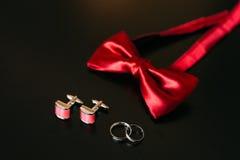 Zapatos negros del novio, corbata de lazo roja, mancuernas, correa, en un bla Imagen de archivo libre de regalías