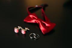 Zapatos negros del novio, corbata de lazo roja, mancuernas, correa, en un bla Imágenes de archivo libres de regalías