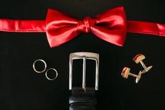 Zapatos negros del novio, corbata de lazo roja, mancuernas, correa, en un bla Foto de archivo