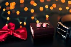 Zapatos negros del novio, corbata de lazo roja, mancuernas, correa, en un bla Fotos de archivo libres de regalías